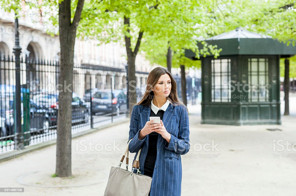 Woman Passing By The City Park With Smartphone In Hands stock photo