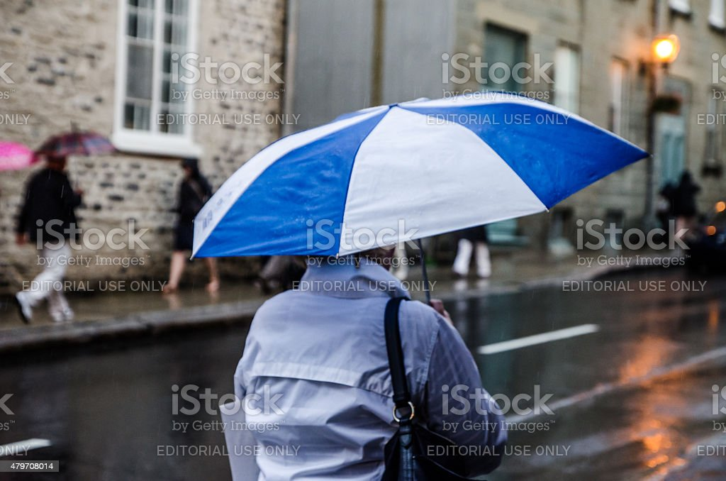 Woman passing with Quebec flag umbrella Flag province of Quebec stock photo