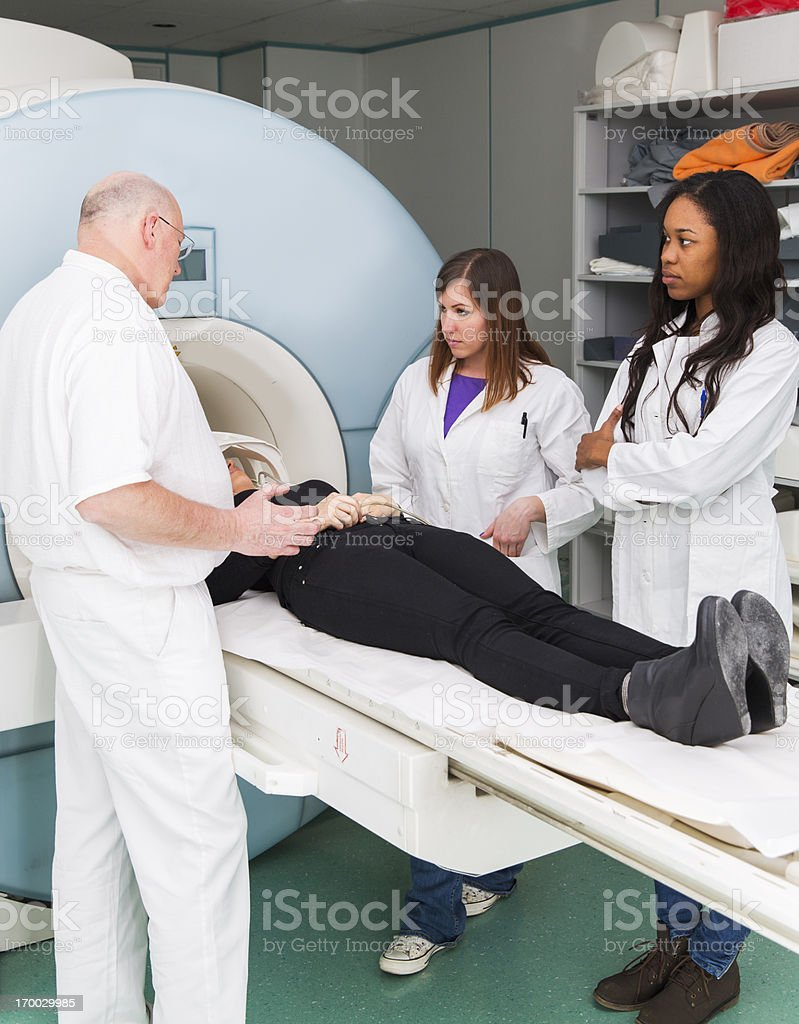 Woman patient having MRI scan,assisting chief radiologist,two doctors royalty-free stock photo