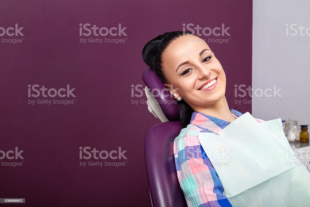 Woman patient with perfect straight white teeth waiting for dentist stock photo