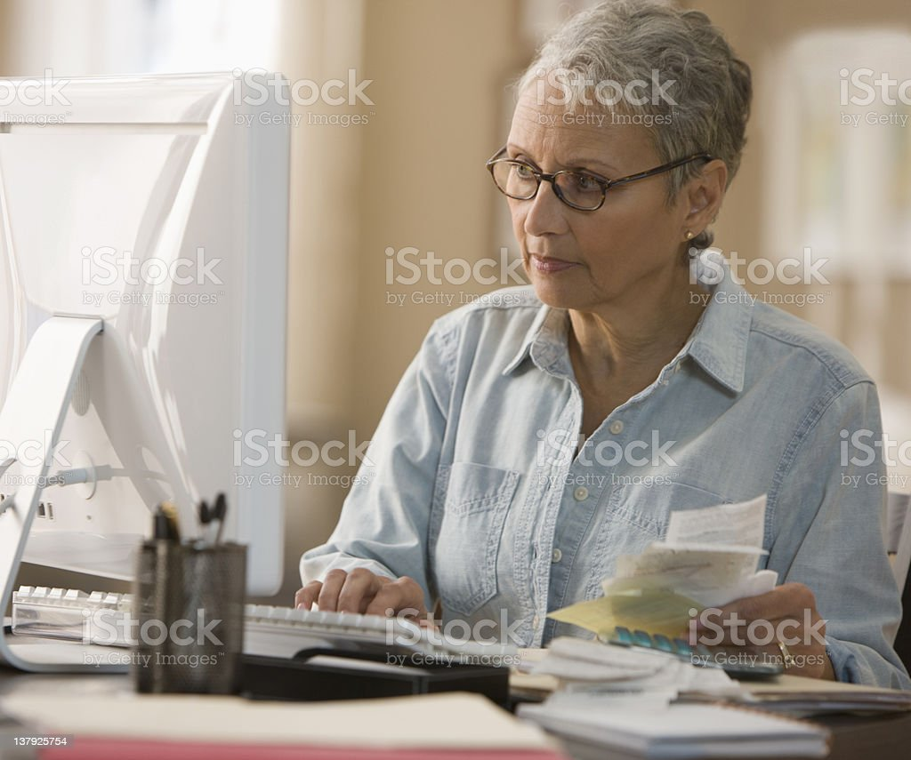 Woman paying bills on computer royalty-free stock photo