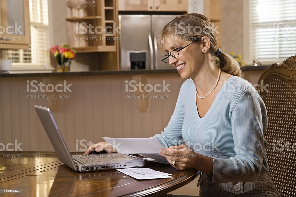 Woman paying bills on computer. stock photo