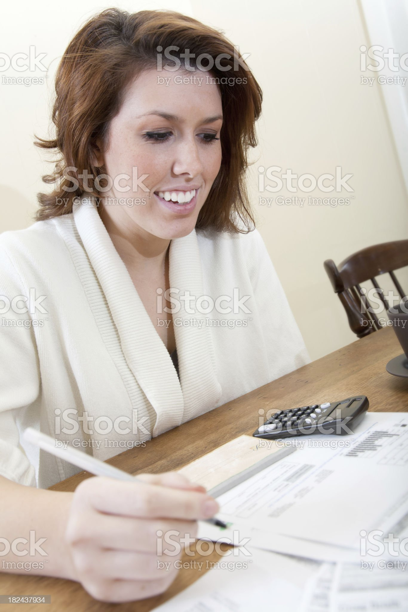 Woman Paying Bills with Check and Calculator royalty-free stock photo
