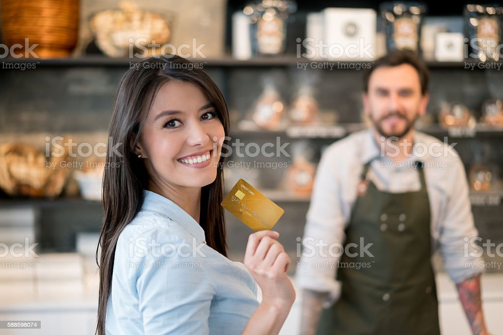 Woman paying by card at the bakery stock photo