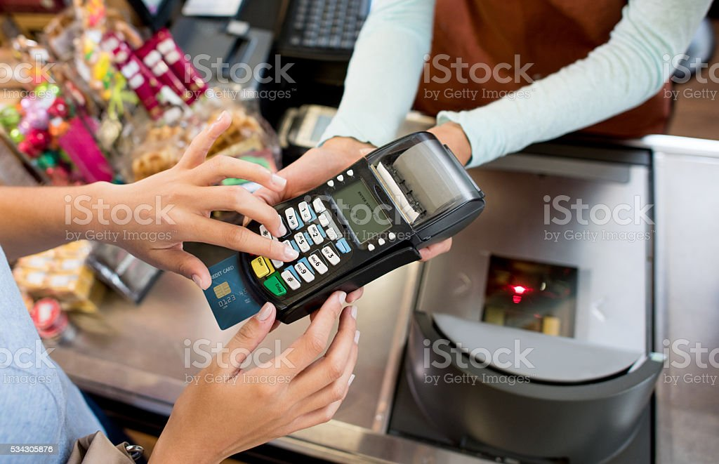 Woman paying by card at the grocery store stock photo