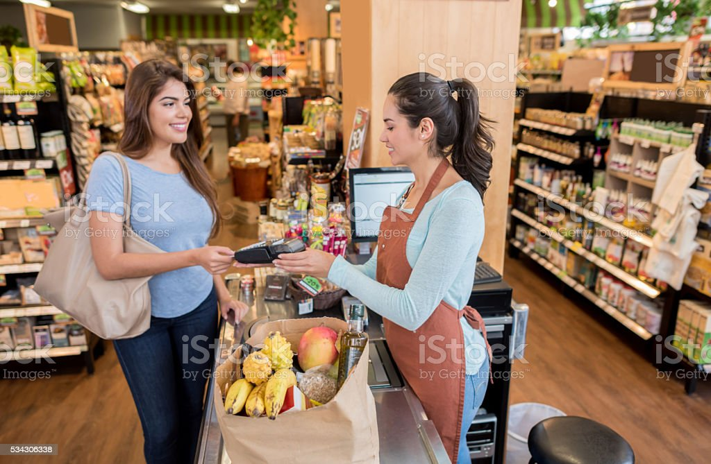 Woman paying by card at the supermarket stock photo