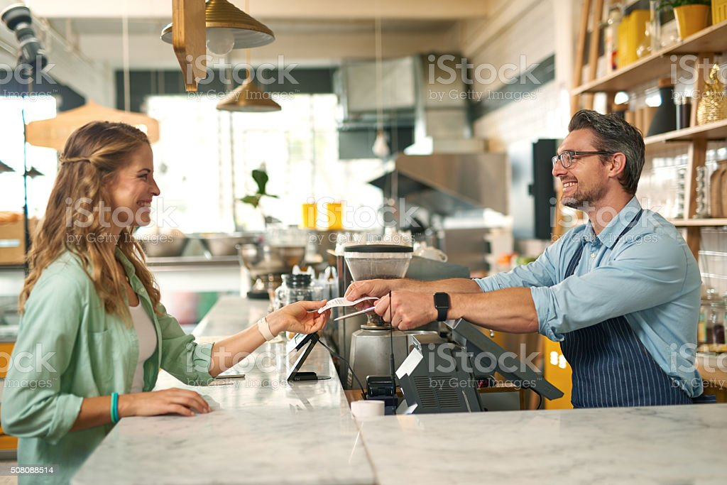 Woman paying for coffee with credit card at cafe stock photo
