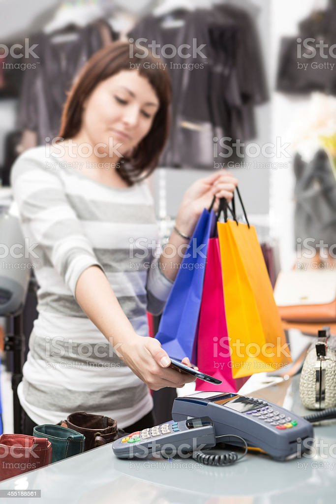 A woman paying for her purchase with an NFC enabled phone stock photo