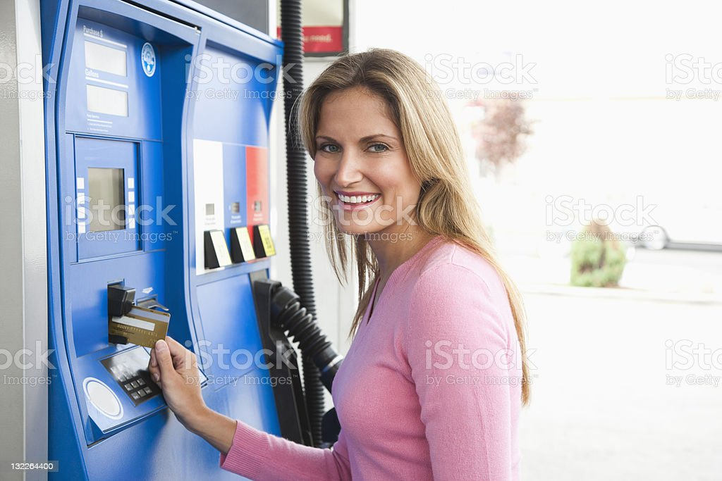 Woman paying gas pump with card royalty-free stock photo