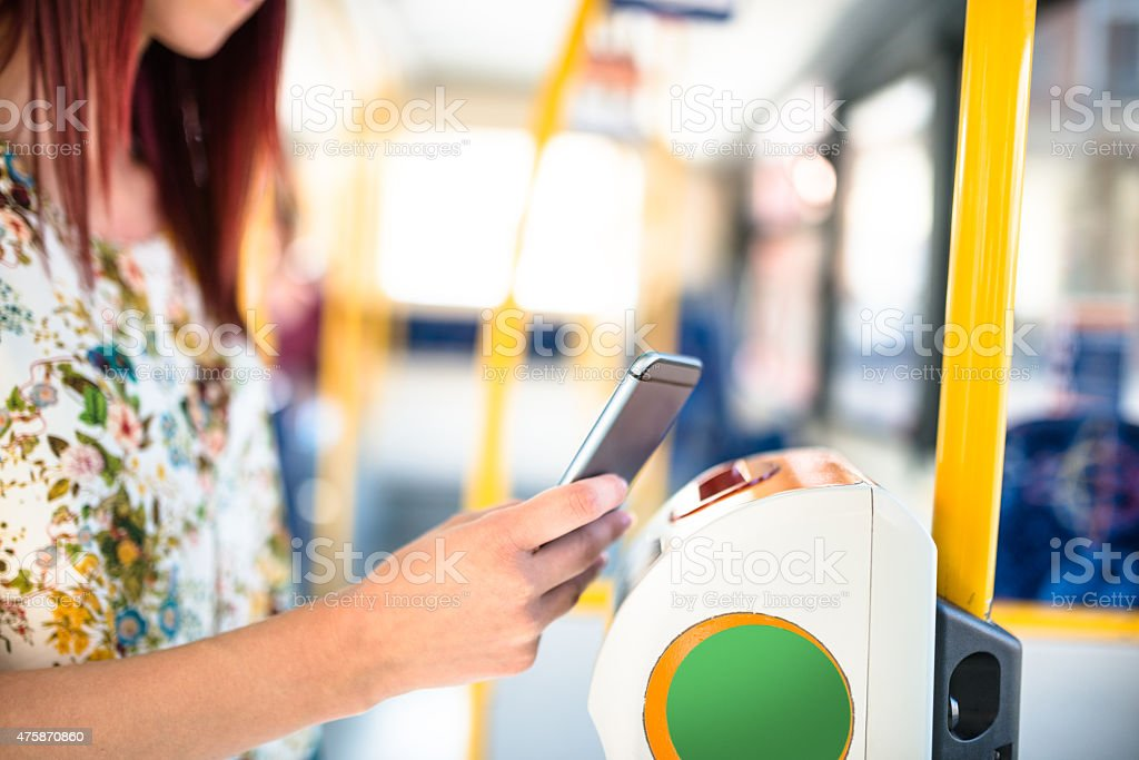 woman paying the bus ticket with the smartphone stock photo
