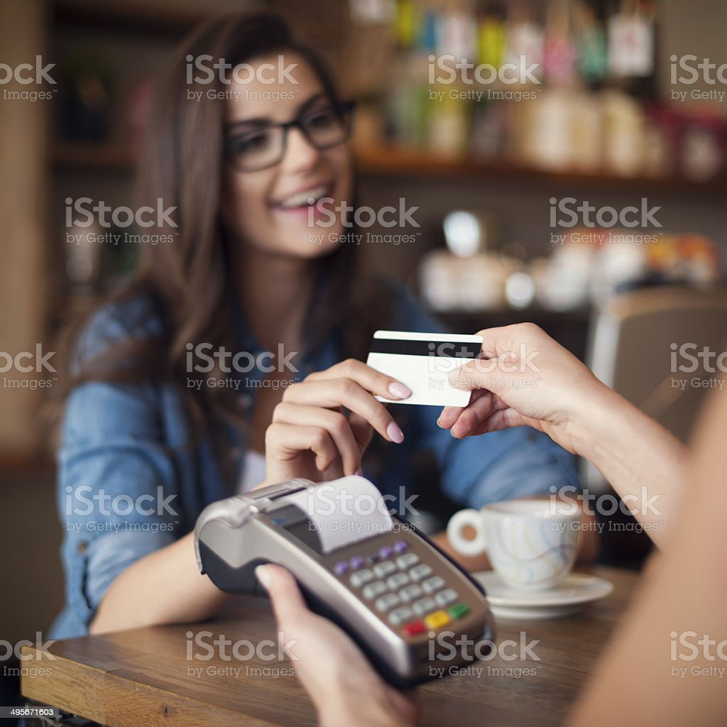 Happy woman paying for cafe by credit card stock photo