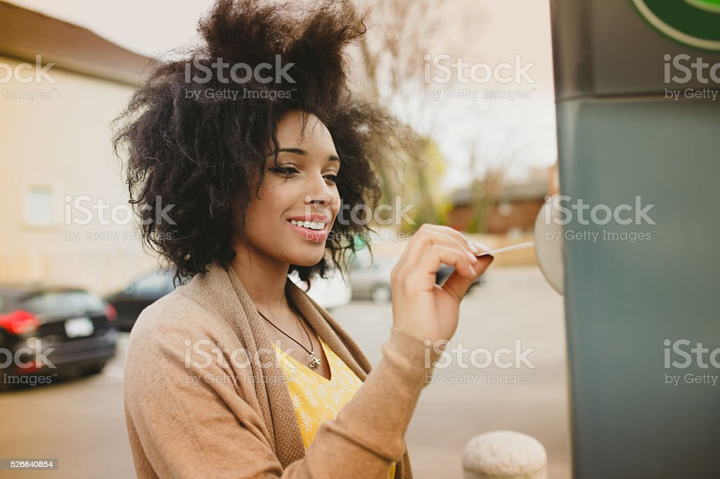 Woman paying with credit card on parking meter stock photo