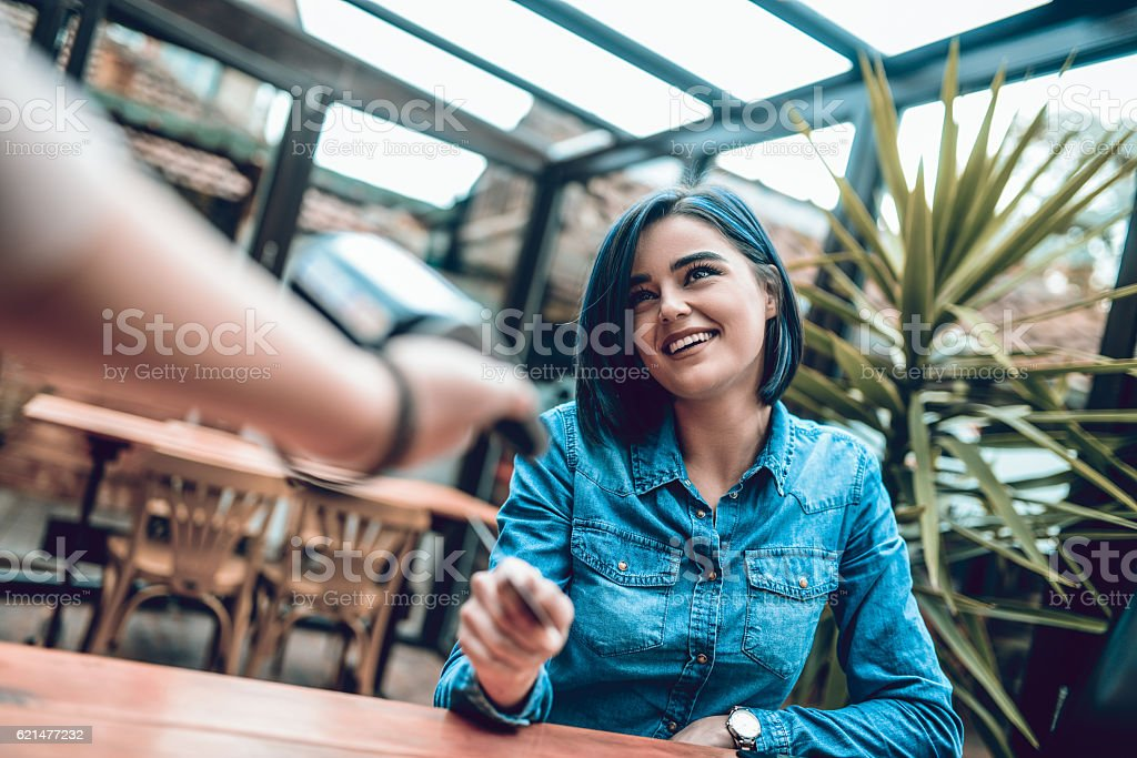 Woman Paying with Credit Card Reader in s Cafe Restaurant stock photo