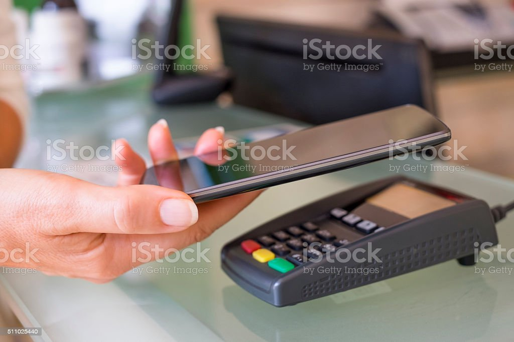 Woman paying with NFC technology on mobile phone at beautician stock photo