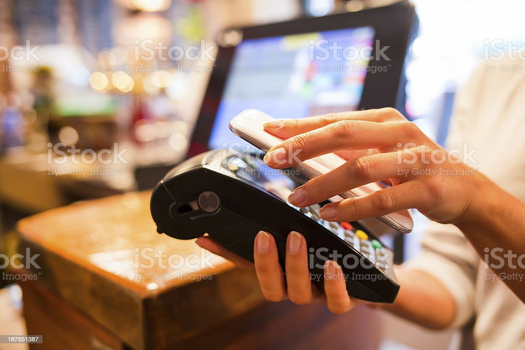 Woman paying with NFC technology on mobile phone in restaurant stock photo