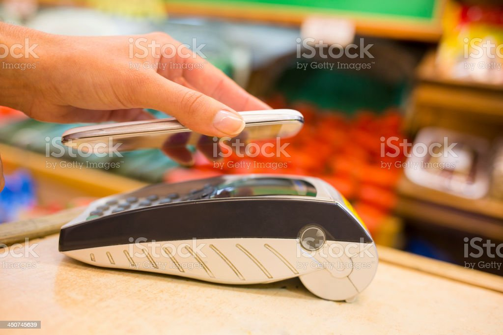 Woman paying with nfc technology on mobile phone stock photo