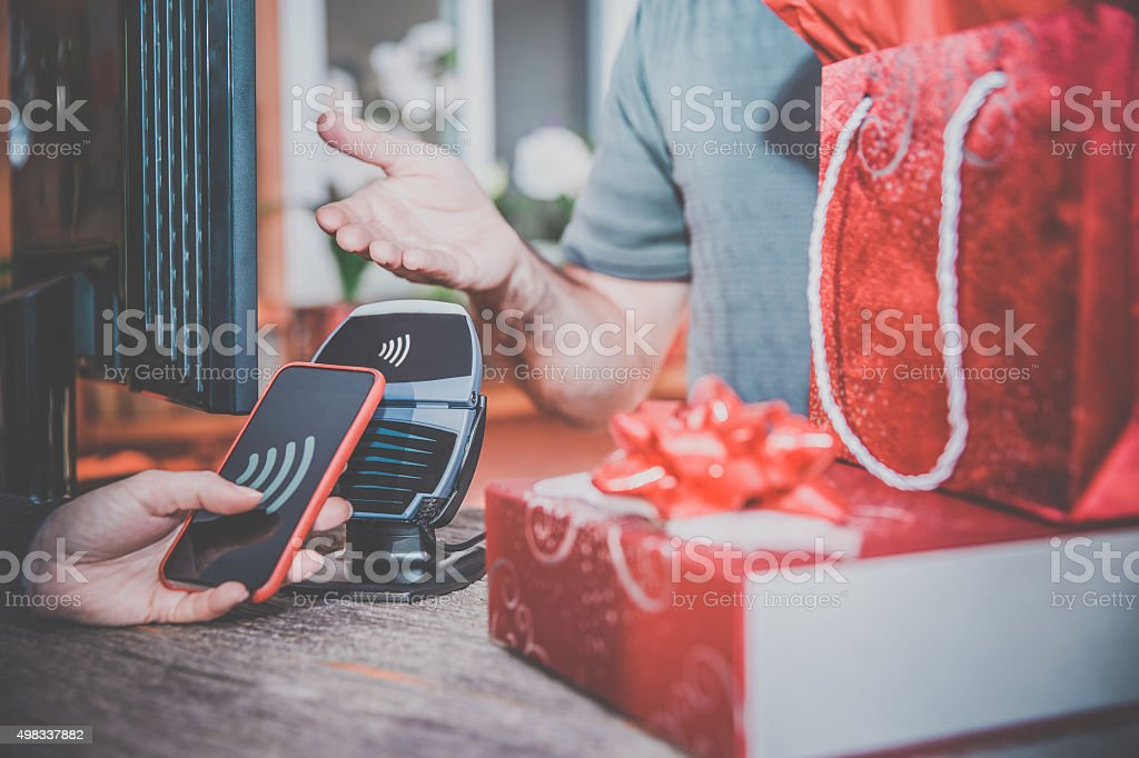 Woman Paying With NFC Technology on Smart Phone in Store stock photo
