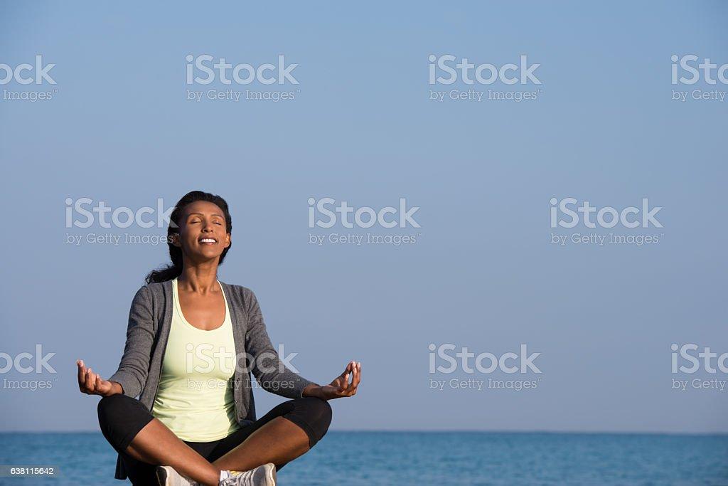 Woman peaceful meditation on seashore. stock photo