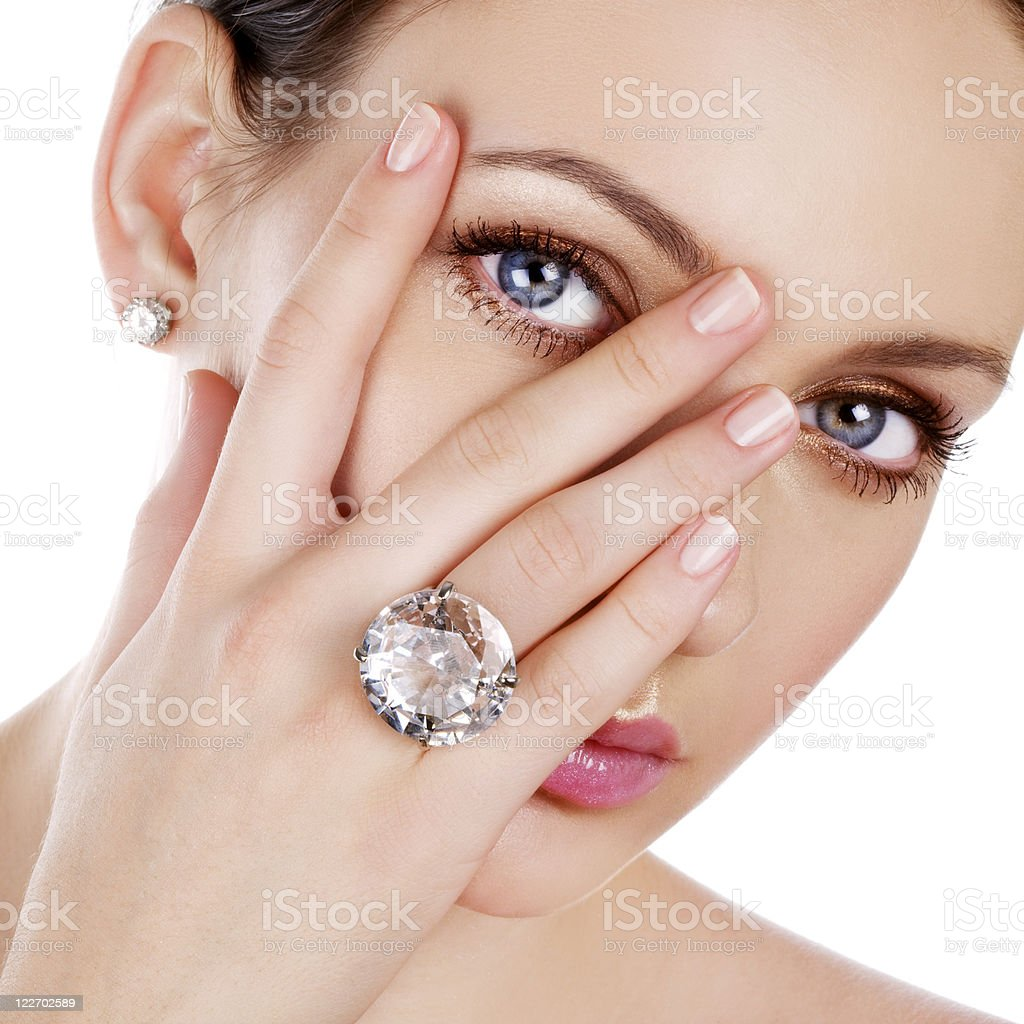 Woman peaking through her fingers to show a diamond ring stock photo