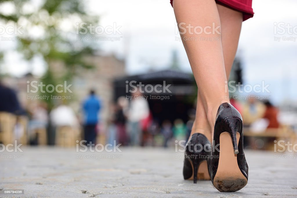 Woman pedestrian on tiled street, cobblestones and high heels stock photo