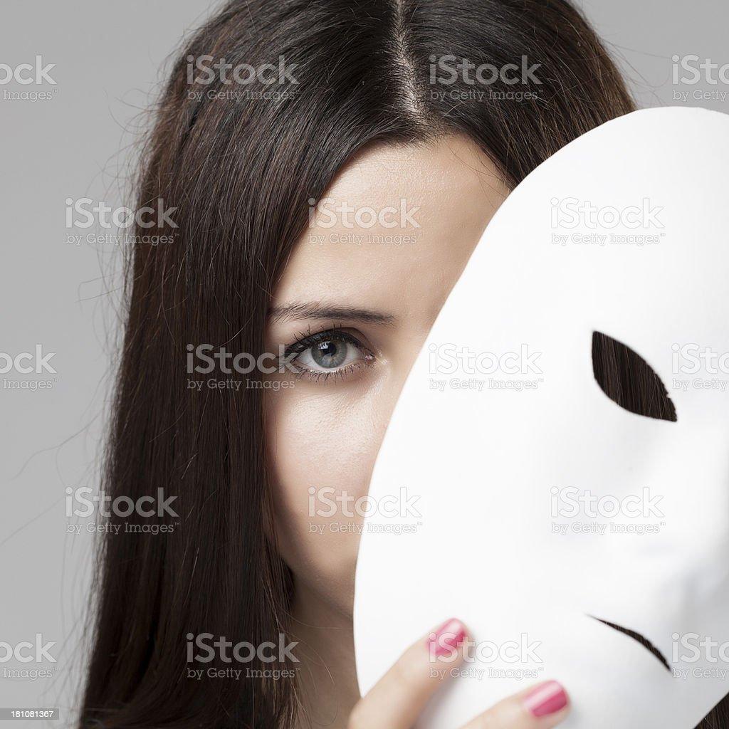 Woman peeking behind mask royalty-free stock photo