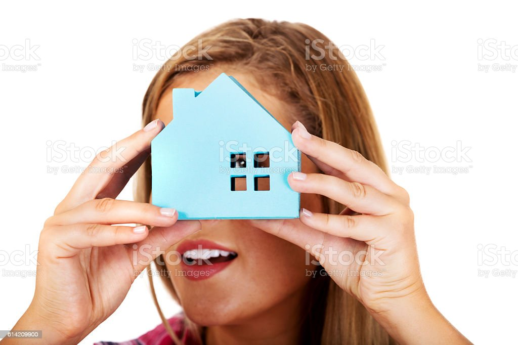 Woman peeks through the window of a paper house stock photo