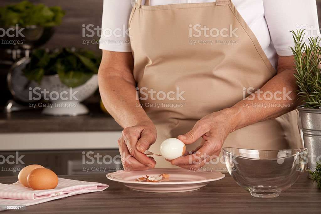 woman peeling eggs stock photo