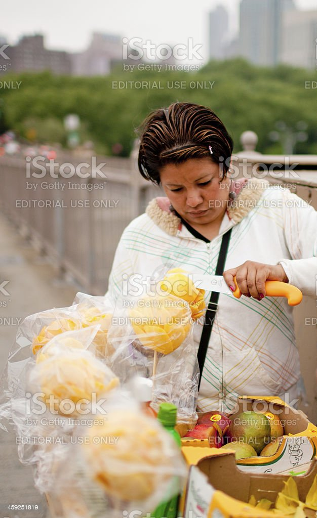 Woman peeling mango for sale on New York street royalty-free stock photo