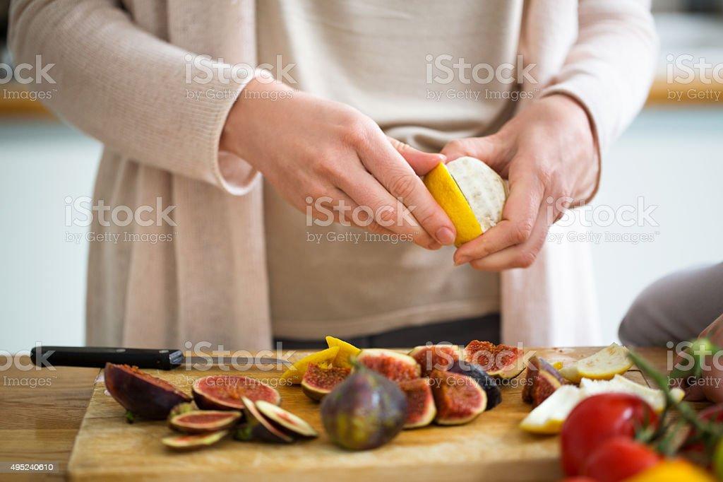 Woman peeling on sweet line in kitchen stock photo