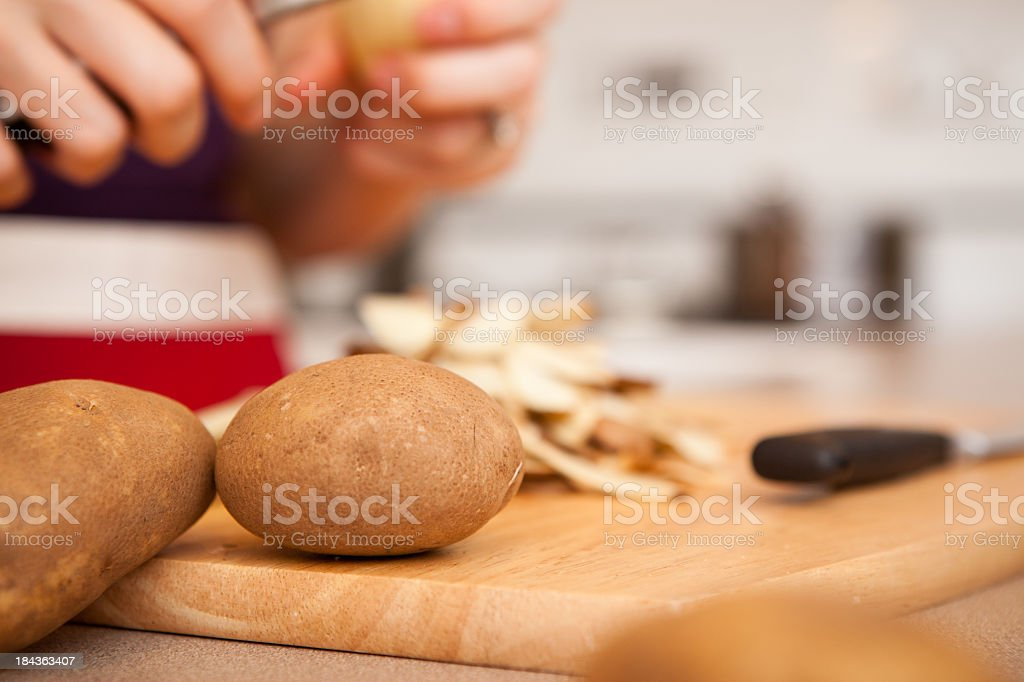 Woman Peeling Russet Potatoes in Kitchen at Home stock photo