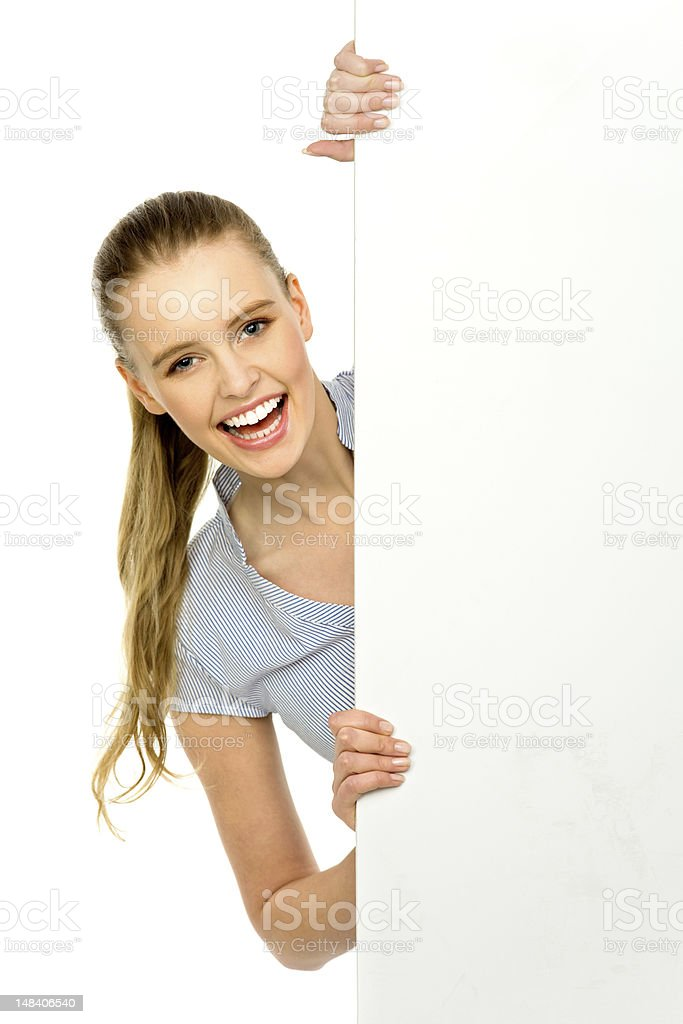 Woman peeping out from behind billboard royalty-free stock photo