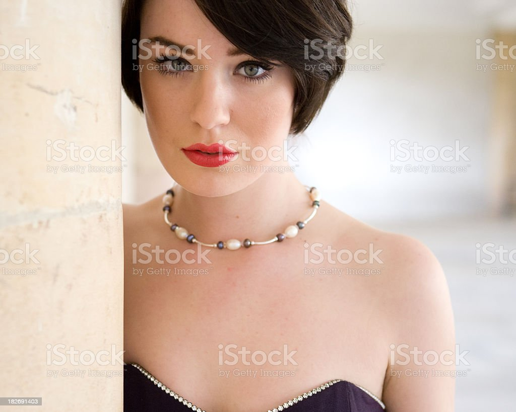Woman peering around a wall dressed elegantly royalty-free stock photo
