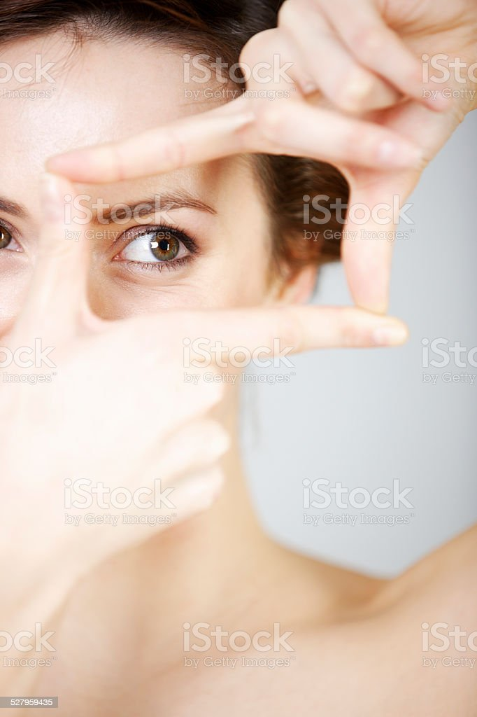 Woman peering though her fingers stock photo