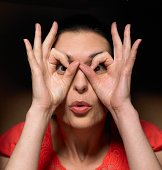 Woman peering through fingers