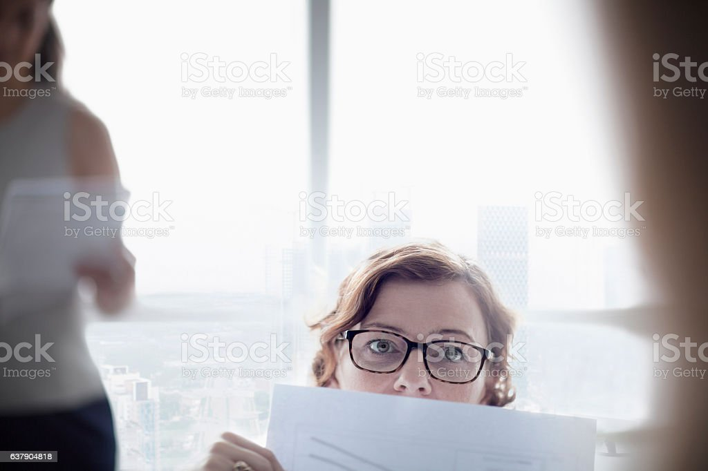 Woman peering up from paper document in meeting stock photo
