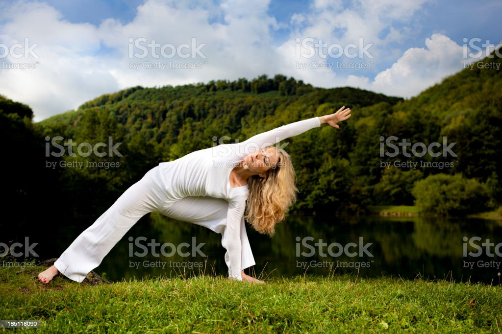 Woman performing a yoga pose outdoors stock photo