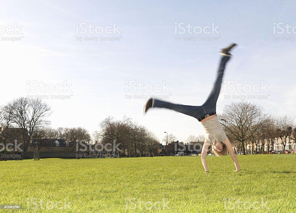 Woman performing cartwheel in park royalty-free stock photo