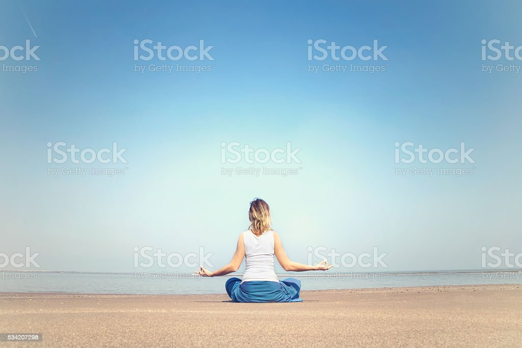 woman performing relaxation and meditation exercises at the sea stock photo