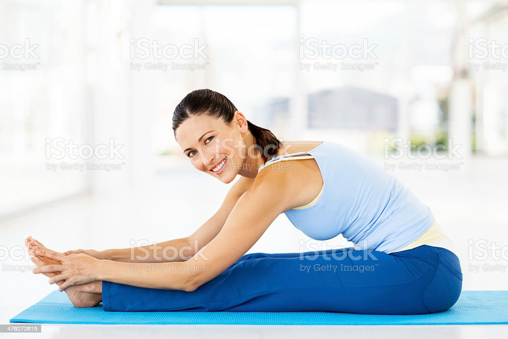 Woman Performing Seated Forward Bend In Yoga Class stock photo