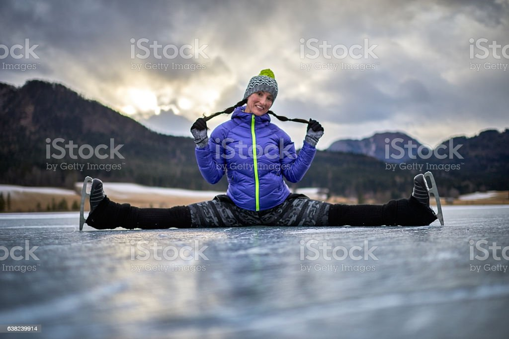 Woman performing split on frozen lake stock photo