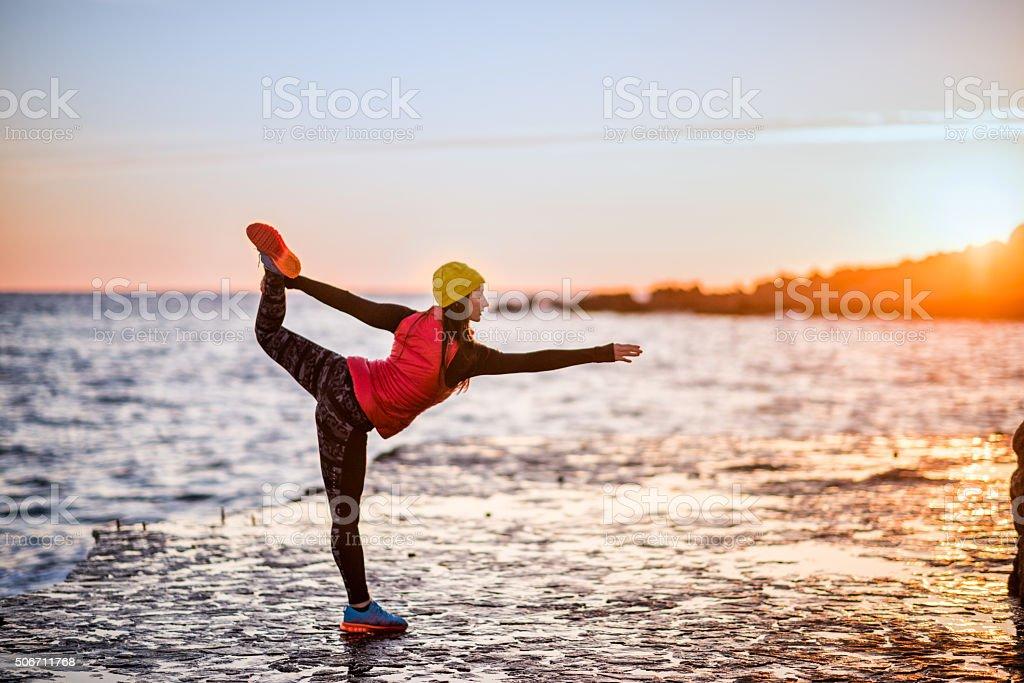 Woman performing yoga exercises near the sea stock photo