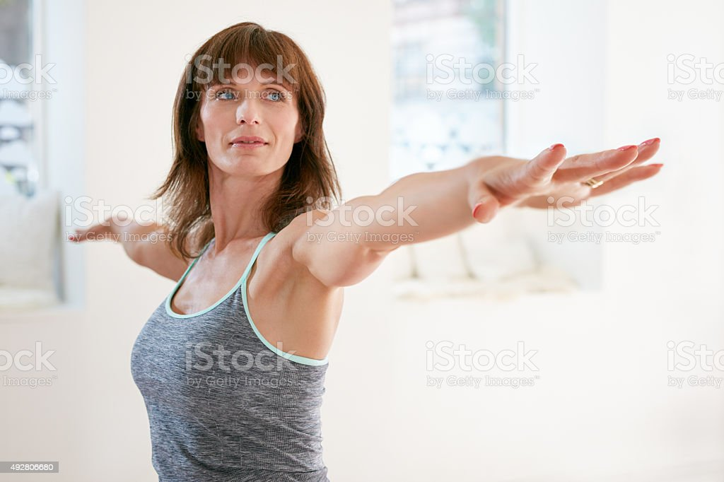 Woman performing yoga in warrior pose stock photo