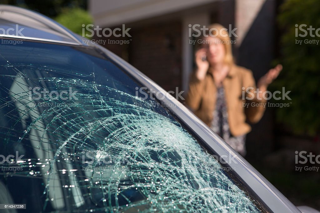 Woman Phoning For Help After Car Windshield Has Broken stock photo