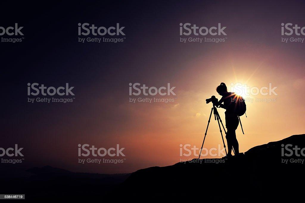 woman photographer taking photo on mountain peak stock photo