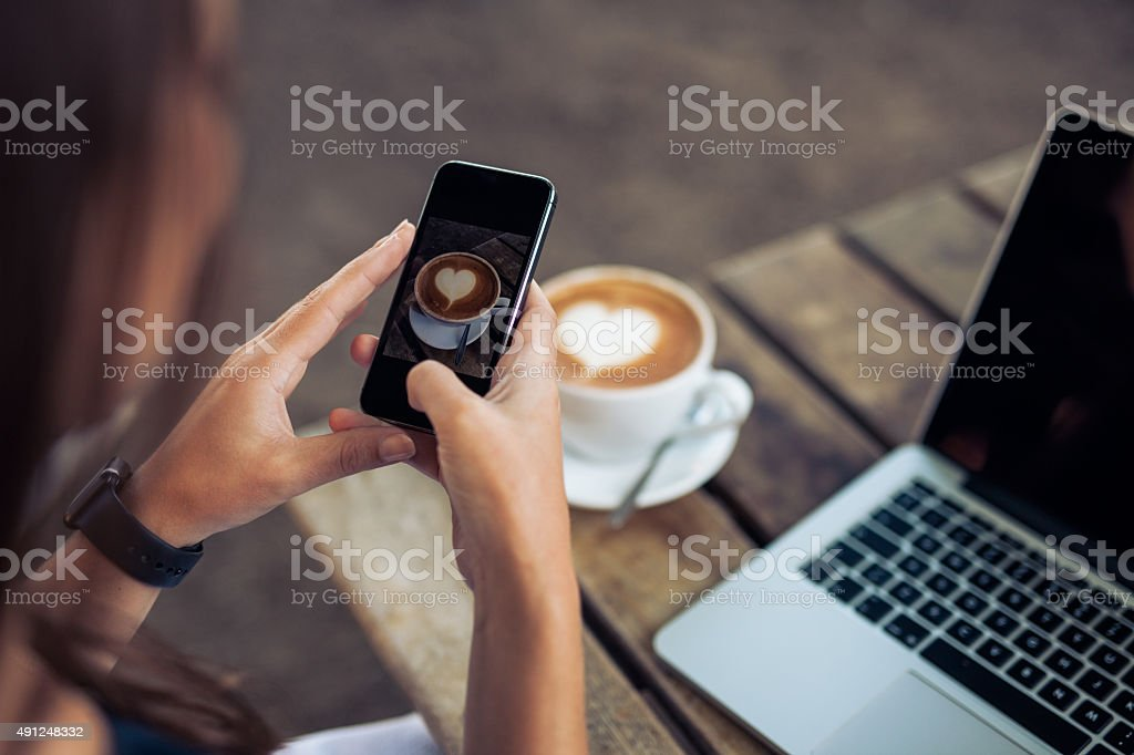 Woman photographing a coffee of cup with smart phone stock photo
