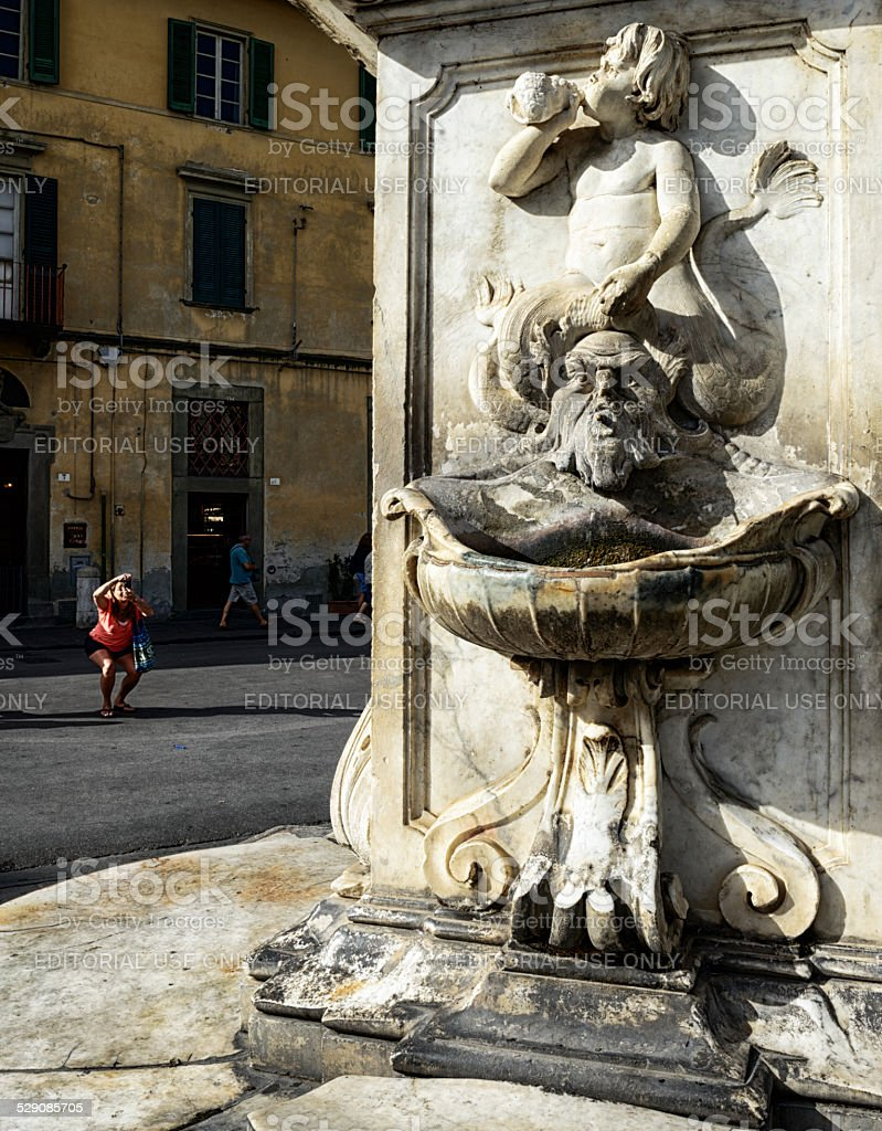 Woman photographing a fountain in Pisa stock photo