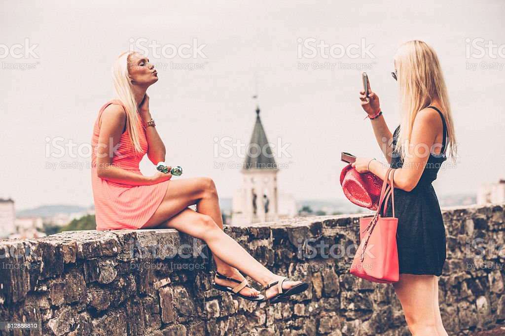 Woman Photographing Friend Blowing a Kiss Outdoors stock photo