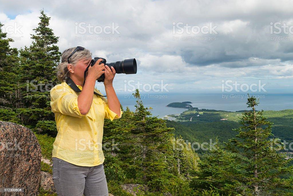 Woman photographing landscape, Cabot trail, Cape Breton, Nova Scotia stock photo