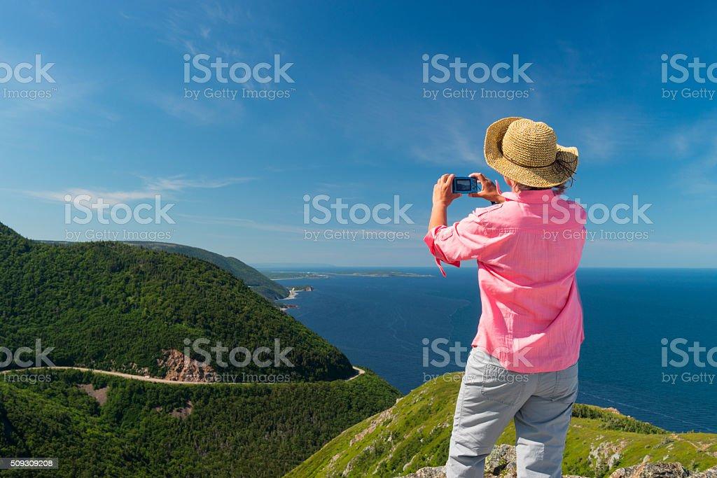 Woman photographing landscape, Skyline, Cabot trail, Cape Breton, Nova Scotia stock photo