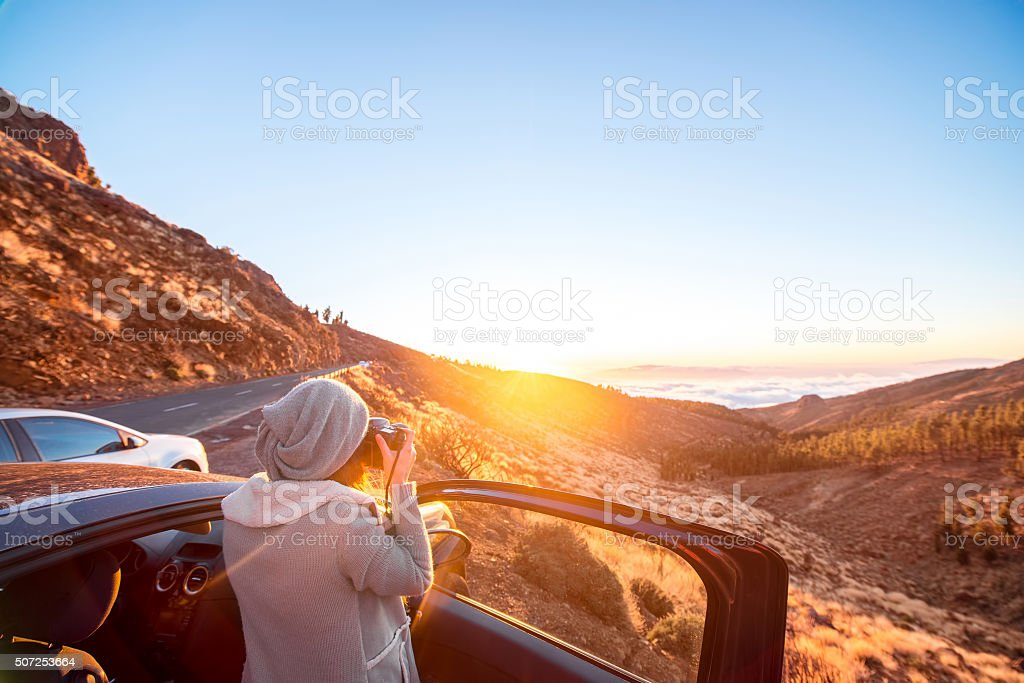 Woman photographing landscape standing near the car stock photo